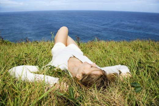 Portrait of young redheaded woman relaxing in grass above the ocean in Maui, Hawaii. : Stock Photo
