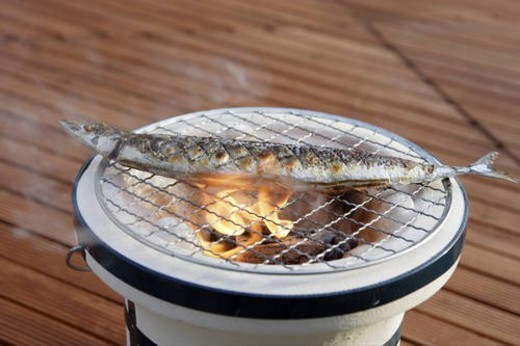 Pacific saury grilling on a charcoal brazier : Stock Photo
