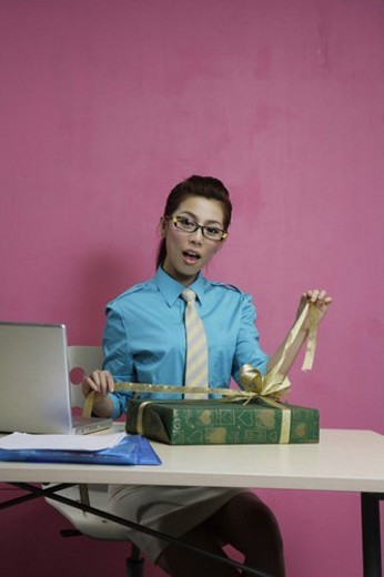 Office woman at desk with a laptop, unlacing a gift box : Stock Photo