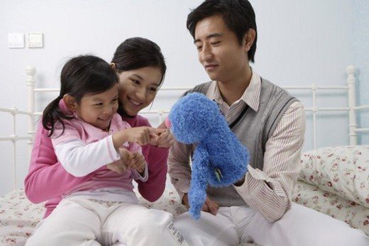 Young mother and daughter playing with a puppet : Stock Photo