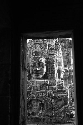 Stone carving of a face on wall at Khmer Kingdom palace ruins : Stock Photo