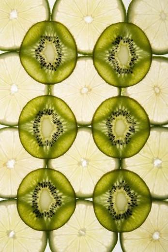 Stock Photo: 4029R-118842 Lime and kiwi fruit slices arranged on white background.