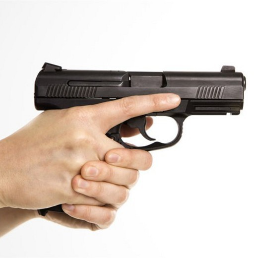 Close up of mid adult female Caucasian law enforcement officer hands on gun aiming. : Stock Photo