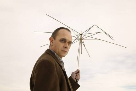 Stock Photo: 4029R-118955 Man holding useless umbrella