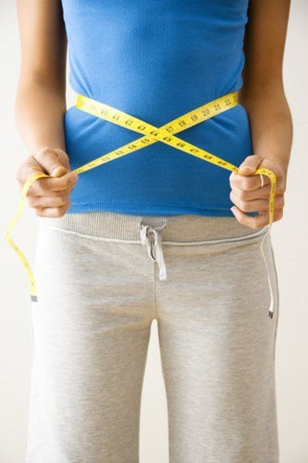 Stock Photo: 4029R-119513 Woman standing pulling measuring tape around waist.