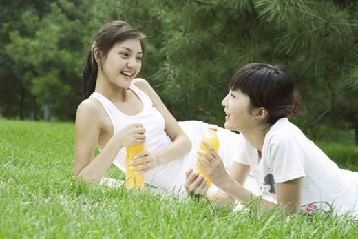 Young women holding orange bottles on lawn, smiling : Stock Photo