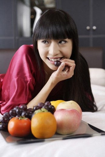 Stock Photo: 4029R-12091 Young woman lying in bed, eating grape