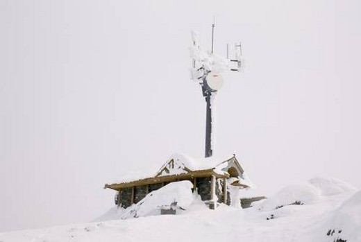 Snow covered building and satellite tower : Stock Photo