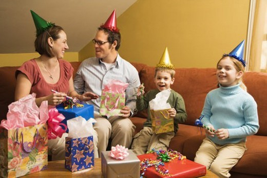Caucasian family wearing party hats and celebrating a birthday party. : Stock Photo