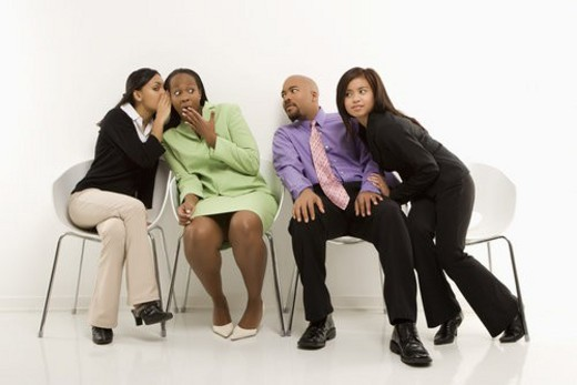 Multi-ethnic businesswomen whispering and making faces while colleagues eavesdrop. : Stock Photo