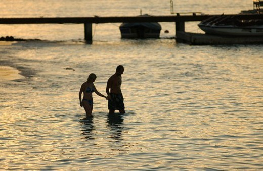 A young couple wading into the sea, Moorea, Tahiti, French Polynesia, South Pacific : Stock Photo