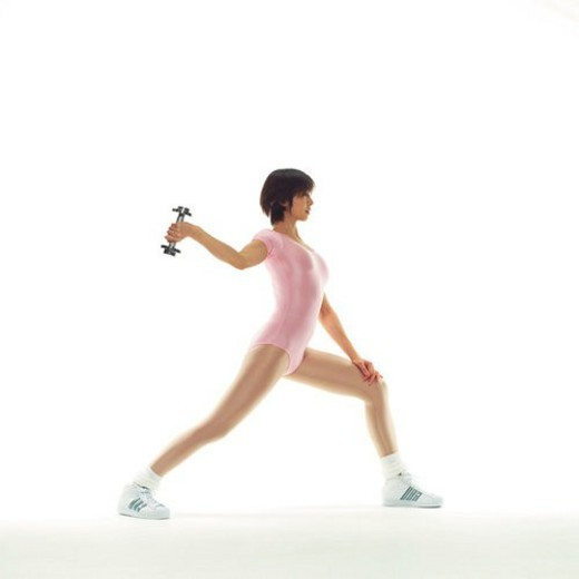 A woman in Leotard exercising with a dumbbell, Side View, Copy Space : Stock Photo