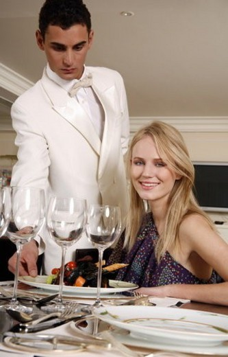 Hotel waiter serving guest : Stock Photo