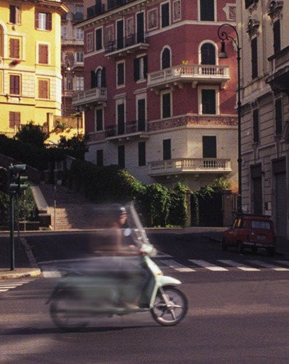 Blurred image of teenager on scooter with backdrop of apartment buildings : Stock Photo