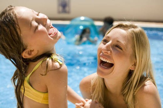 Mother and daughter playing in pool : Stock Photo