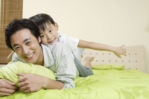 Stock Photo: 4029R-127877 Son riding on father on bed