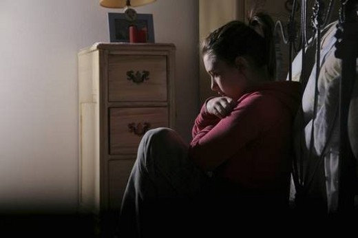 Teenage girl sitting at the foot of her bed : Stock Photo