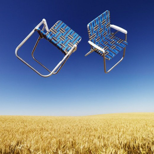 Two lawn chairs in mid-air above a field of wheat with blue sky. : Stock Photo