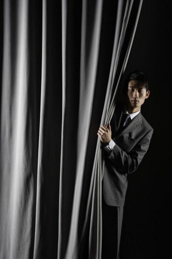 Business man posing with black curtain : Stock Photo