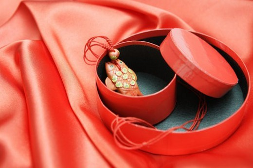 Still life of red silk,casket and pisces necklace : Stock Photo