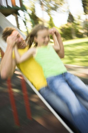 Father and daughter on slide : Stock Photo
