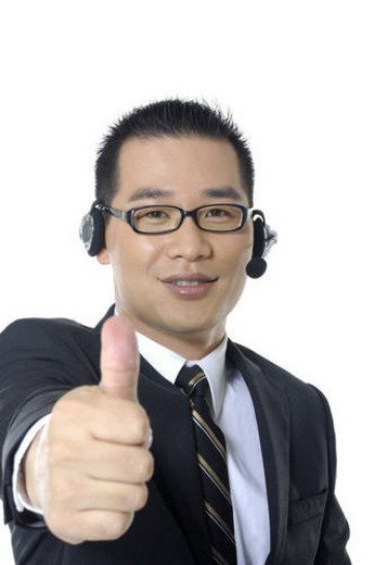Portrait of a male customer care executive showing thumbs up : Stock Photo