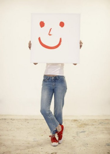 Young woman holding drawing of smiley face : Stock Photo