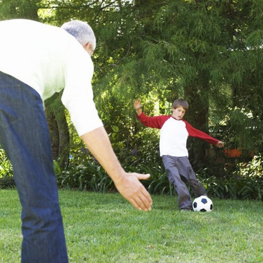Stock Photo: 4029R-140734 Father and son playing football in a garden