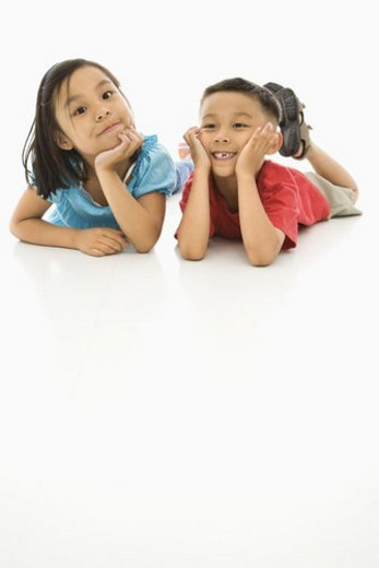 Asian brother and sister lying on floor with heads on hands. : Stock Photo