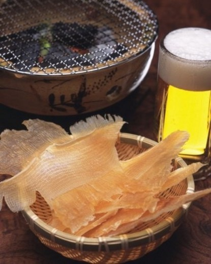 Stock Photo: 4029R-142368 Closed Up Image of a Typical Japanese Snack, Some Dried Fish Next to a Small Grill and a Glass of Beer, High Angle View