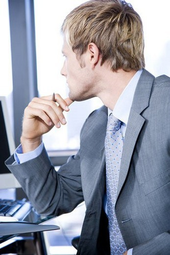 Close up of a businessman looking thoughtful in a modern office : Stock Photo