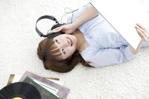 Young woman lying on her back listening to music : Stock Photo