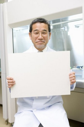 Portrait of a mature scientist man holding a white board, front view : Stock Photo