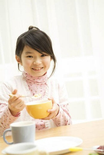 Stock Photo: 4029R-146166 Young girl eating breakfast