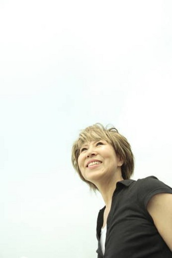 Mature woman smiling under sky, copy space : Stock Photo