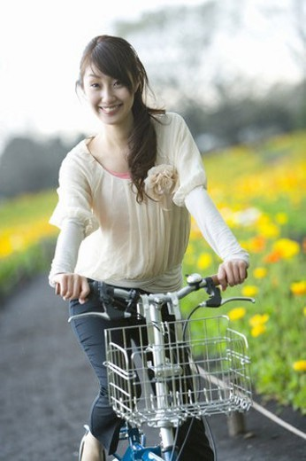 Young Woman Riding on Bicycle, Differential Focus, Front View : Stock Photo