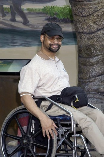 Man with a disability, utilizing a wheelchair for mobility, smiling and posing for the camera. : Stock Photo