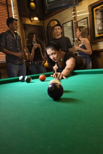 Stock Photo: 4029R-15042 Young caucasian woman preparing to hit pool ball while playing billiards.