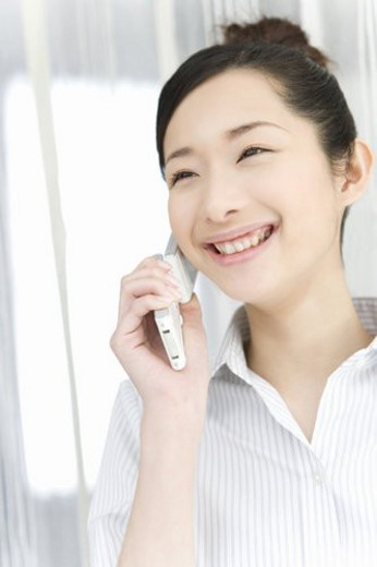 Woman smiling and using mobile phone, front view : Stock Photo