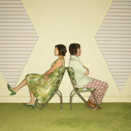 Caucasian mid-adult couple wearing vintage clothing sitting back to back in green vinyl chairs with arms crossed. : Stock Photo