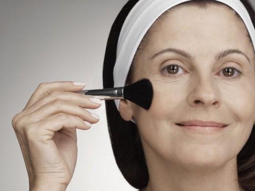 Woman applying make-up with brush : Stock Photo