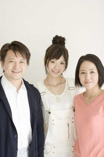 Stock Photo: 4029R-154685 Portrait of family, smiling and looking at camera, front view, white background