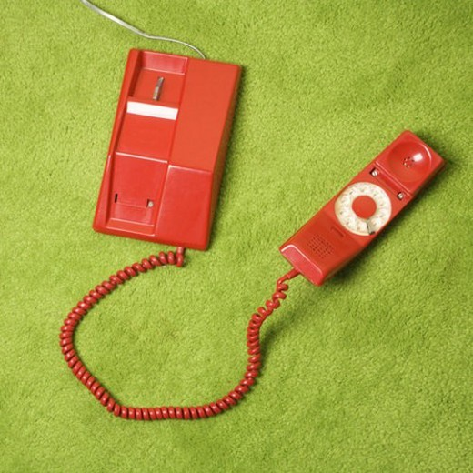 Stock Photo: 4029R-154954 Red vintage rotary telephone on 70 s green carpet.