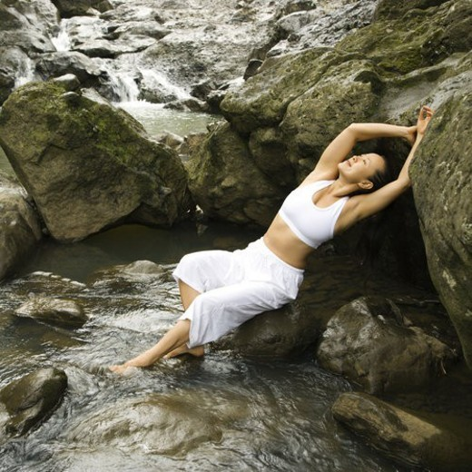 Asian American woman leaning back on boulder in creek in Maui, Hawaii. : Stock Photo