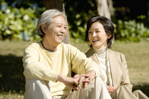 Stock Photo: 4029R-158116 A Mature Couple Sitting on the Ground and Talking, Front View, Three Quarter Length