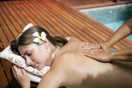 Side view of a young woman getting massage. : Stock Photo