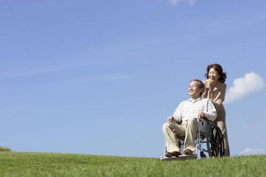 Stock Photo: 4029R-160541 Senior woman pushing her husband in wheelchair at the park