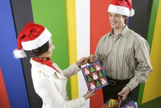 Young man giving Christmas present to young woman : Stock Photo