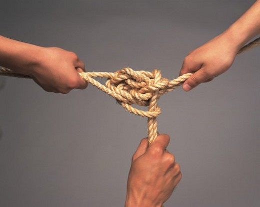 Stock Photo: 4029R-162524 Three hands pulling a tied rope, High Angle View