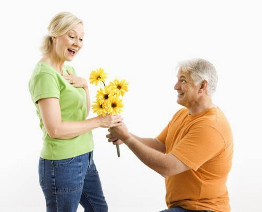 Middle-aged man on bended knee giving woman bouquet of yellow flowers. : Stock Photo